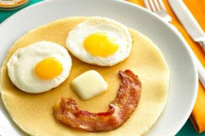 Eggs, bacon and pancakes arranged in a smiley face