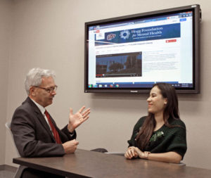 Mark Lusk, Ed.D., left, talks with a pre-nursing student about online training modules