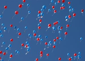 red and blue balloons floating up to the heavens