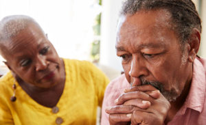 minority men mental health - Older African American man and woman, man appearing despondent
