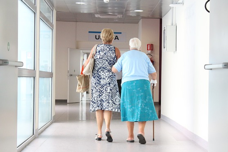 Woman and elderly mother walking down a hospital hallway