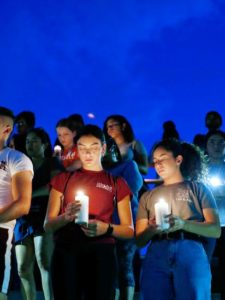 People holding candles after mass shooting