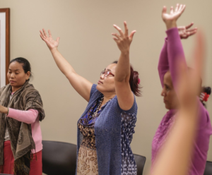 3 women raising their arms in worship