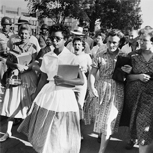 Elizabeth Eckford ignores the hostile screams and stares of fellow students on her first day of school. She was one of the nine Black students whose integration into Little Rock's Central High School was ordered by a Federal Court following legal action by NAACP.