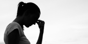 A stock photo of a woman's silhouette with her hand to her face.