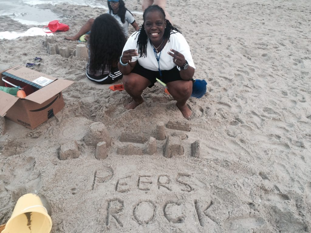 "A PeerFest attendee at the beach poses for the camera. ""Peers Rock"" is spelled out in the sand."