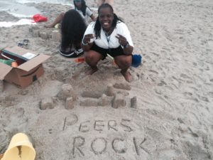 """A PeerFest attendee at the beach poses for the camera. """"Peers Rock"""" is spelled out in the sand."""