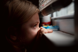 Photo of a little girl peaking through the window blinds for children mental health month