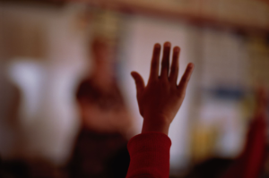 COVID-19 and Our Schools, photo of child's hand up in classroom